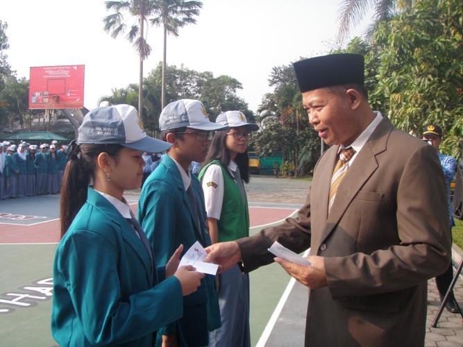 Bapak Kepala SMAN 10 Malang menyerahkan hadiah apresiasi atas prestasi siswa